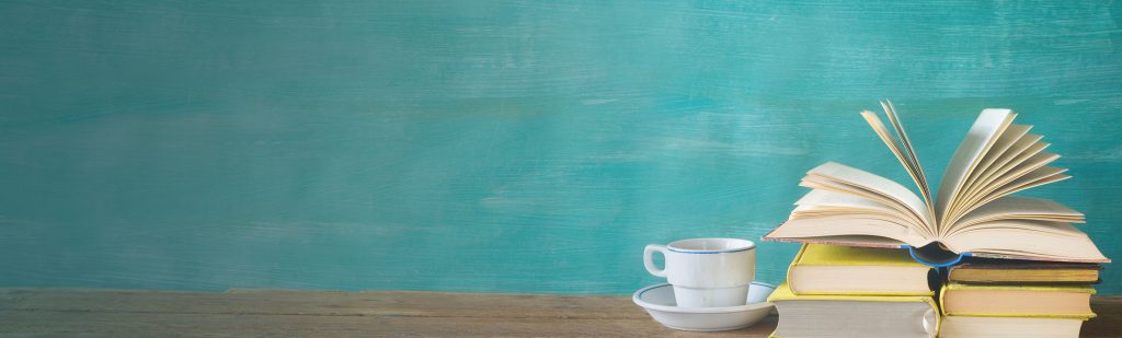 Photo of stack of books and coffee cup against a teal wall